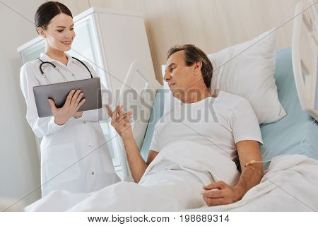 My diagnosis. Sad ill man pointing at the tablet and talking to the doctor while asking about his diagnosis