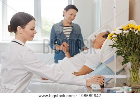 Time for taking medicine. Pleasant cheerful female doctor taking a bottle with medicine and smiling while treating her patient