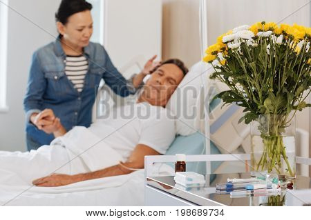 Nice present. Selective focus of a beautiful flower bouquet standing on the table in the hospital room