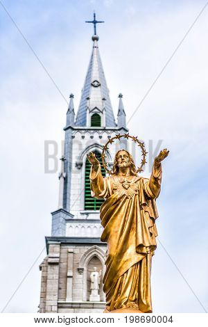 Batiscan Canada - May 29 2017: Parish of Saint Francois Xavier de Batiscan in small town on Chemin du Roy with closeup of gold Jesus Christ statue