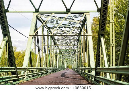 Old green metal bridge on Chemin du Roy highway in Quebec Canada in summer with cars