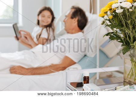 Hospital room. Selective focus of bedside table with medicine on it with nice pleasant father and daughter talking in the background