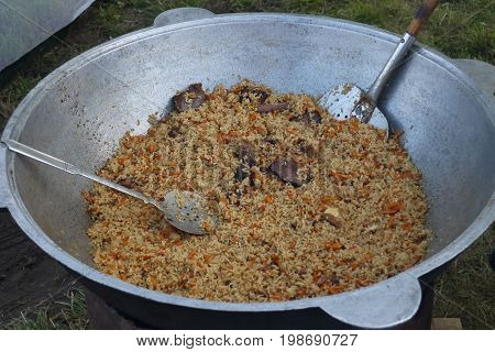 Pilaf with rice and meat cooked in a pig-iron copper