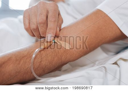 Hospital treatment. Close up of the IV catheter being inserted into the patients vein while being hooked up to the IV