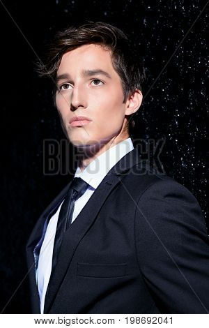 Portrait of a handsome young man posing in black suit and white shirt over black background. Male beauty, fashion. Hair styling.