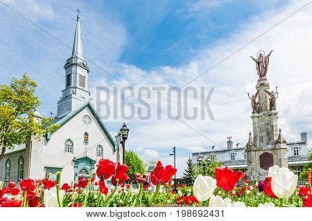 Saint-Augustin-de-Desmaures Canada - May 29 2017: Parish of Sainte Augustin in small town on Chemin du Roy with statue of Jesus Christ and colorful tulips