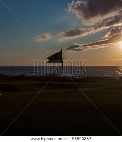 Silhouette of a golf flag in Cape Breton Nova Scotia