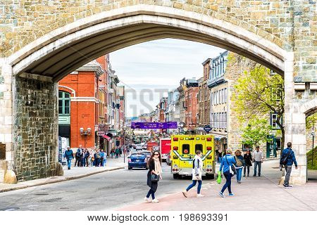 Quebec City Canada - May 29 2017: Saint John's Gate Fortress entrance to old town street with cars and people walking