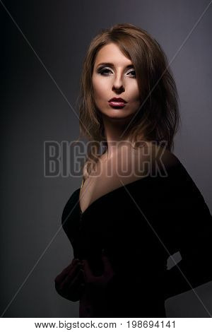 Beautiful Woman With Elegant Neck And Nude Shoulder In Fashion Black Clothing Looking Mystic And Cal