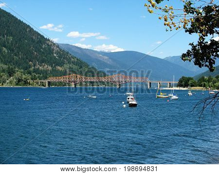 View of steel bridge over Kootenay River in Nelson, BC with boats in the water and mountain background