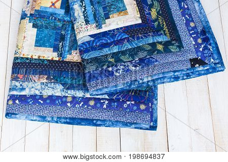 sewing, needlework, geometric, garment industry, cosiness, comfort concept - deep blue colored plaid sewed of textile squares with magnificent print on white wooden boards