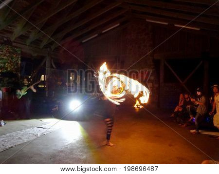 OAHU - APRIL 22 2017: Fire Dancer Alexis Aaron spins fire around her body as people watch during at Optimysstique 2017 Earthday under a open air pavilion at Camp Erdman on the North Shore of Oahu.
