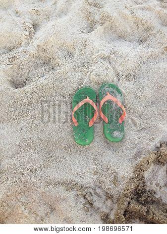 Summer vacation concept. Green Orange Flipflops on a sandy ocean beach