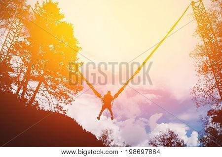 Man jumping on a rope up on a slingshot device. High contrast, silhouette of a man. Shine of the sun.