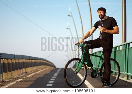 The smiling male bicyclist is using phone with earphones outdoors on the bridge.