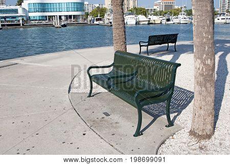 Metal benches painted green at the Sarasota marina near the ocean, on a sunny afternoon. Sarasota, Florida, USA.