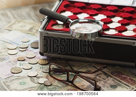 Different Old Collector's Coins With A Magnifying Glass