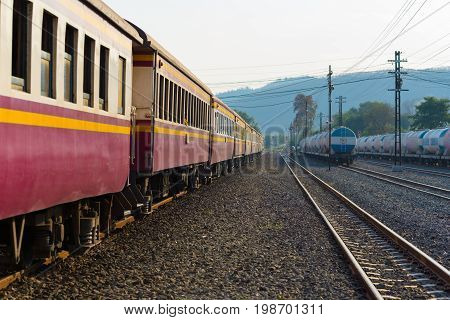 Saraburi, Thailand - February 15, 2017: Passenger train of Thai Railways. The nearest purple car is in the focus, other things dissolve into nice bokeh. This is a second class sitting car of a train Ubon Ratchathani - Bangkok (Thailand)
