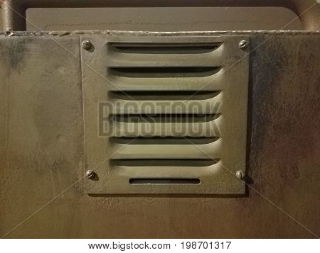 small square metal vent with four screws in it