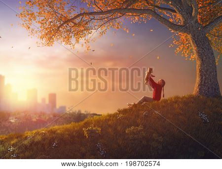 Cute little happy girl walking in autumn Park. Pretty child enjoys the beautiful autumn nature. Kid playing with teddy bear.