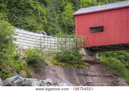 Old Vintage Red Covered Bridge, White Brick Wall, Tall Pine Trees And Large Rock