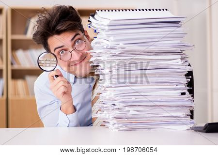 Funny auditor checking reports with magnifying glass