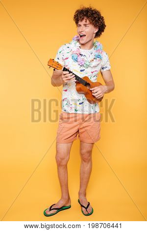 Full length portrait of a young happy guy in summer clothes playing ukulele and singing isolated over yellow background