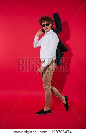 Full length of a young charming man in sunglasses walking with jacket over shoulder isolated over red background