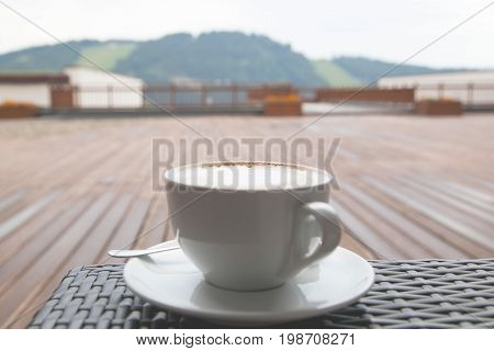 Soft focus close up cup of capuccino latte coffee on wood background mountain view