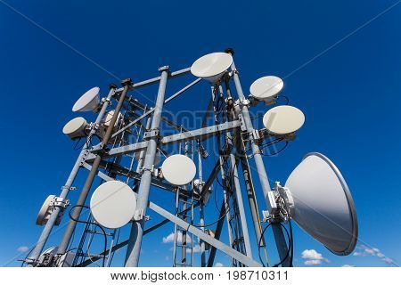 Telecommunication tower with microwave antennas and satellite dishes with cables and fiber optic against blue sky