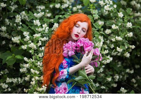 Girl with pale skin and long red hair in peony dress on background of a flower garden. Beautiful girl with red lips with a bouquet of peonies in hands in garden. Beauty makeup and white flowers garden background. Redhead girl in garden. Sensual girl portr