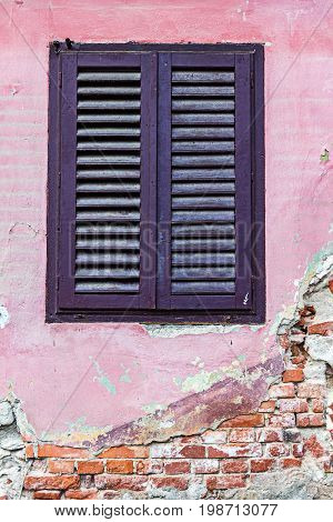 Detail of facade with shuttered old window in neglected ancient house in Sibiu city Romania.