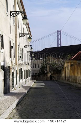 Quiet street in Lisbon with the capital's famous bridge in the background