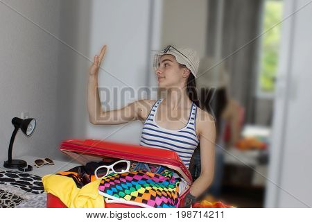 Young Girl dreaming of a world trip. Young girl packing suitcases on floor at home. Girl ready for summer vacation