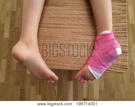 View of child's foot in plaster and bandage on wooden background