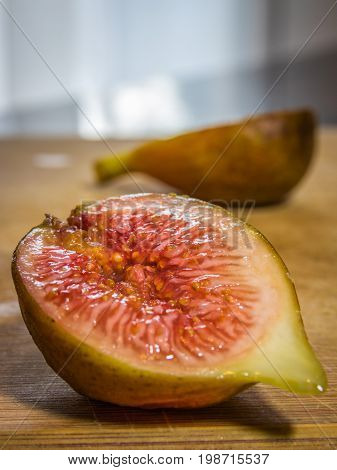 Vertical close up of the inside of half of a fig on a wooden cutting board on a kitchen counter with the other half in soft focus in the background