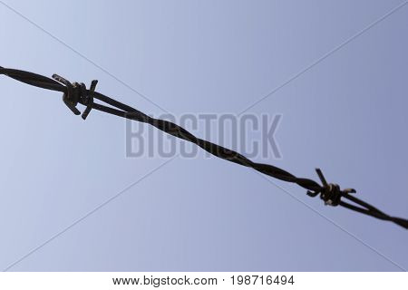 Barbed wire shown against the blue sky