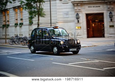 LONDON, UK - SEP 27: Vintage taxi in street on September 27, 2013 in London, UK. London is the world's most visited city and the capital of UK.