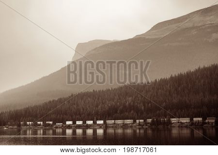 BANFF, CANADA - AUGUST 27: Cargo train, lake and mountain on August 27, 2015 in Banff National Park, Canada. Established in 1885, it is the oldest park in Canada.
