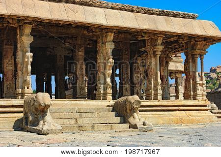 Lions in the foreground guard Bala Krishna Temple at ancient ruins of Hampi, Karnataka, India. Old and famous Indian landmark, World Heritage.