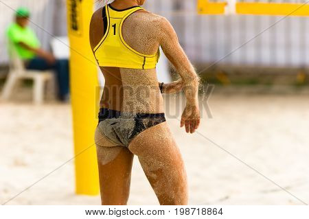 Volleyball player beach is a beach volleyball player dusting the sandy sand off her body after taking a dive..