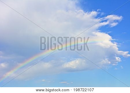 Rainbow under the white cloud on the azure sky. Azure sky with a rainbow and a cloud.