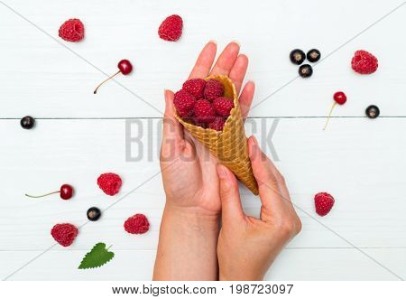 Top View Of Sweet Fresh Organic Raspberries In Waffle Cones And One Cone In Girl's Hands. Fresh Berr