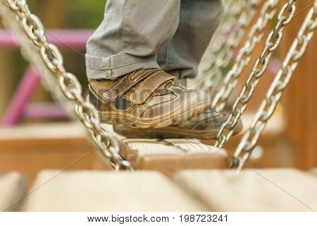 Child playing at the attractions of the swings in the park legs close-up