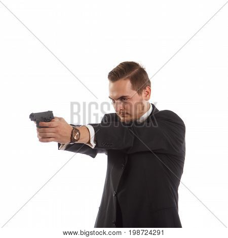 A man in a suit aiming his handgun