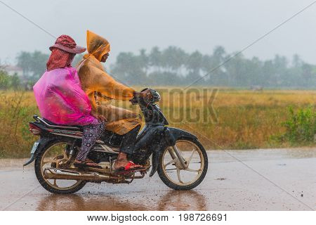 Kampot, Cambodia - December 14, 2016: Two people (unidentified) in pink and orange packable raincoats ride scooter while heavy raining. Palm trees seen in rainy haze.