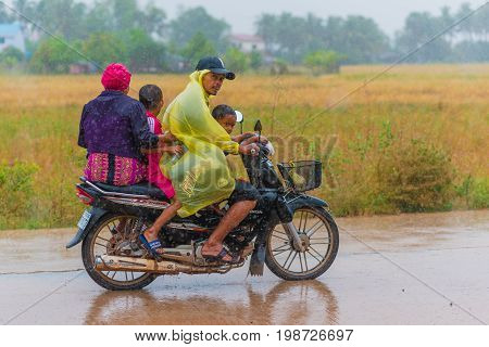 Kampot, Cambodia - December 14, 2016: Cambodian family (unidentified) rides a scooter foursome (two adults, two children) while getting wet in heavy rain.