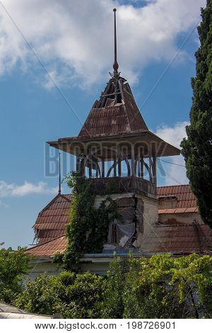 Tower of old beautifull abandoned mansion overgrown by plants and trees. Sukhum, Abkhazia