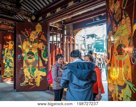 Shanghai, China - Nov 6, 2016: Gate to the 600-year-old Old City God Temple. Paintings of the City Gods on gate doors. Visitors enter and exit through this gate.