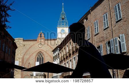 Silhouette of a young man riding a bicycle on Gambetta Square in Perpignan.